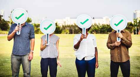 four people holding green check signs standing on the field photography